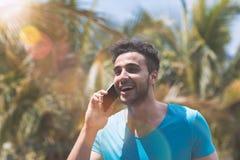 Telefonema de fala do homem latino-americano sobre o latim tropical Guy Speaking Holding Mobile da raça de Forest Background Happ fotografia de stock royalty free