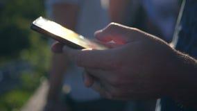 Telefonen är i händerna av en man som fångar strålarna av solen och exponerar in i kameran HD 1920x1080 långsamt arkivfilmer