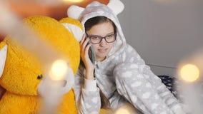 Telefoneren de warme pyjama's die van de meisjestiener op een cel spreken met een vriend bij de Kerstmisvakantie stock videobeelden