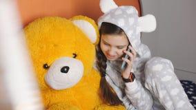 Telefoneren de warme pyjama's die van de meisjestiener op een cel spreken met een vriend terwijl het zitten in bed met een Teddyb stock videobeelden