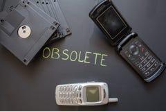 Telefones celulares e disquetes velhos no fundo escuro fotografia de stock