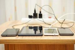 Telefones celulares e tabuleta que carregam na mesa Imagens de Stock Royalty Free