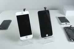 Telefones celulares modernos diferentes com a tela quebrada na tabela branca fotografia de stock royalty free