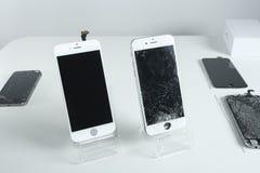 Telefones celulares modernos diferentes com a tela quebrada na tabela branca Fotos de Stock
