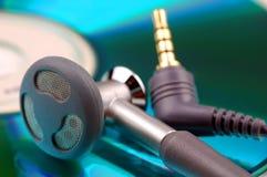 Telefones da orelha e plugue de Jack no fundo cd colorido Imagens de Stock