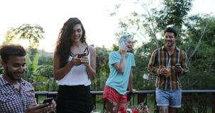 Telefones espertos da pilha do uso do grupo dos povos que falam o assento na tabela fora em meios sociais de sorriso felizes dos  video estoque