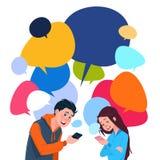 Telefones espertos novos da pilha de terra arrendada da mensagem do menino e da menina sobre bolhas coloridas do bate-papo Foto de Stock