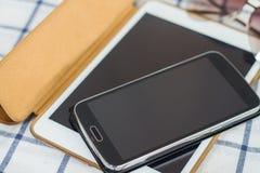 Telefones espertos, tabuletas na tabela Foto de Stock