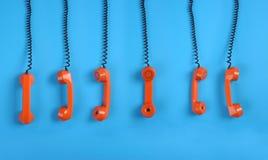 Telefoni arancioni sopra priorità bassa blu Immagine Stock
