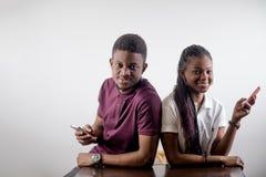 Telefoni cellulari africani della tenuta delle coppie in una mano Immagini Stock