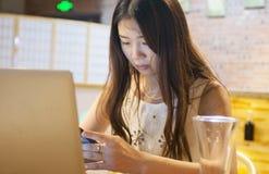 Telefoni cellulari asiatici di uso delle ragazze fotografie stock libere da diritti