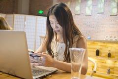 Telefoni cellulari asiatici di uso delle ragazze fotografia stock