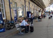 Telefoni cellulari di uso dei viaggiatori alla stazione di Huddersfield fotografie stock libere da diritti