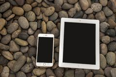 Telefoni cellulari e compressa che sono disposti su un mucchio delle pietre fotografia stock libera da diritti