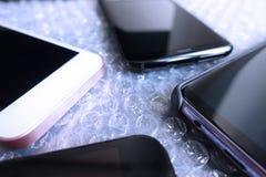 Telefoni cellulari o smartphone sulla stagnola della bolla di protezione come fondo Fotografie Stock