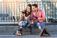 Telefoni cellulari sorridenti della tenuta delle coppie Fotografia Stock