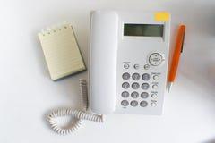 Telefoni con carta e la penna su un fondo bianco per uso professionale Fotografia Stock Libera da Diritti