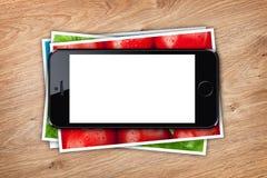 Telefoni con lo schermo in bianco sopra la pila di collage stampato delle immagini Immagine Stock