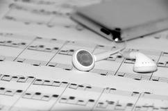 Telefoni dell'orecchio sulle note musicali Immagini Stock