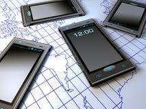Telefoni delle cellule sopra il programma di mondo Fotografie Stock