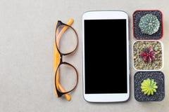 Telefoni i vetri e il topview mobili del cactus sui copys marroni della tavola Immagini Stock Libere da Diritti
