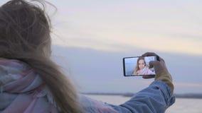 Telefoni la macchina fotografica che incita la ragazza per affrontare le foto sulla spiaggia stock footage