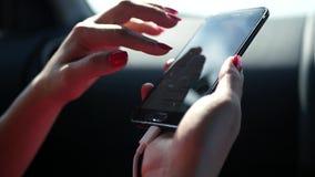 Telefoni nelle mani di una donna nell'automobile, la ragazza clicca sopra lo schermo HD, 1920x1080 Movimento lento archivi video