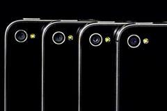 4 telefoni neri che mostrano le loro macchine fotografiche Fotografie Stock Libere da Diritti