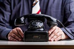 Telefoni su priorità alta con le mani di un impiegato di concetto Immagine Stock