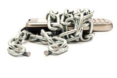 Telefoni in una catena su una priorità bassa bianca Fotografia Stock
