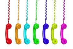 Telefoni variopinti che pendono da un cavo Fotografie Stock