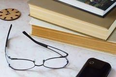 Telefonieren Sie, alte Bücher, Uhrikone auf dem Desktop Stockfotografie