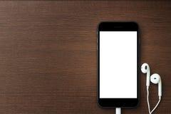 Telefonleerer bildschirm und -kopfhörer auf hölzerner Tabelle Stockfotos