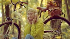 Telefonmusik H?stkvinnan i h?st parkerar med den gr?na sweatern H?rlurarbegrepp enjoy attraktiv kvinna f?r st?ende f?r nakenhet f stock video