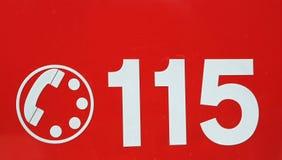Telefonnummer 115 på röd bakgrund av brandkåren i den Arkivfoto