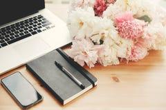 Telefono alla moda con le peonie bianche vuote dello schermo, del computer portatile, del taccuino, della penna, di rosa e sulla  immagine stock libera da diritti
