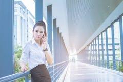 Telefono asiatico che parla, riunioni di chiamata della donna di affari fra i quadri fra l'attesa sopra sui marciapiedi Commercio fotografie stock
