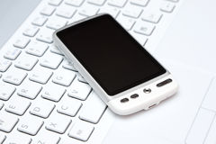 Telefono astuto sopra la tastiera bianca Fotografia Stock Libera da Diritti