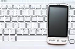Telefono astuto sopra la tastiera bianca Fotografie Stock Libere da Diritti