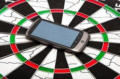 Telefono astuto sul dartboard fotografia stock