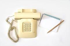 Telefono beige dell'isolato il vecchio con il tubo del cavo si trova su fondo bianco fotografia stock libera da diritti