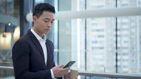 Telefono bevente della tenuta del caff? del giovane uomo d'affari asiatico nel centro di affari stock footage