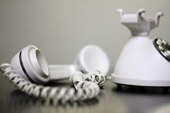 Telefono bianco antiquato fuori dal gancio Fotografie Stock