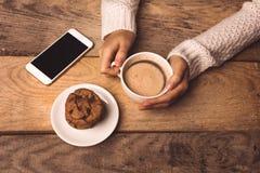 Telefono bianco, una tazza di caffè nelle mani della ragazza, biscotti sulla tavola immagini stock libere da diritti