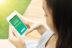 Telefono cellulare asiatico della tenuta della mano della donna con le valutazioni di cliente Immagini Stock Libere da Diritti