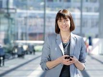 Telefono cellulare astuto della tenuta della donna di affari immagini stock