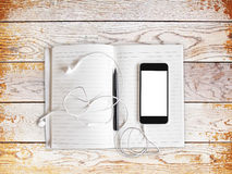 Telefono cellulare in bianco con i headhones e diario su una tavola di legno Immagini Stock