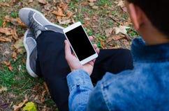 Telefono cellulare bianco a disposizione un giovane uomo di affari dei pantaloni a vita bassa che si siede e che esamina telefono Fotografia Stock