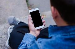 Telefono cellulare bianco a disposizione un giovane uomo di affari dei pantaloni a vita bassa che si siede e che esamina telefono fotografia stock libera da diritti