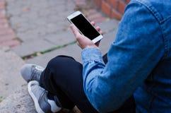 Telefono cellulare bianco a disposizione un giovane uomo di affari dei pantaloni a vita bassa che si siede e che esamina telefono Immagine Stock Libera da Diritti